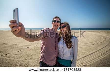 Couple Takes Picture of Themselves on Beach - stock photo