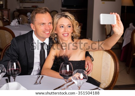 Couple taking a picture of themselves at restaurant