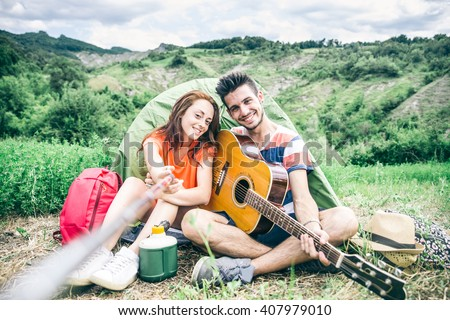Couple taking a selfie in a campsite  - Young people having fun while trekking in the nature - stock photo