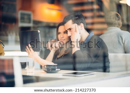 Couple taking a selfie with tablet computer in cafe - stock photo