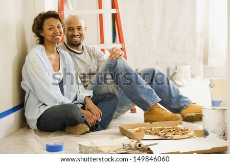 Couple taking lunch break from painting - stock photo