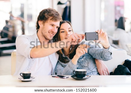 Couple taking photo of themselves with a phone in cafe - stock photo