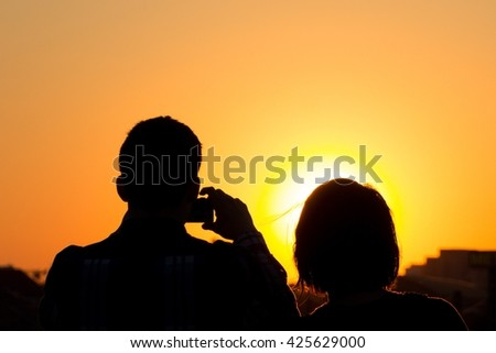 couple taking picture of sunset sky - silhouette