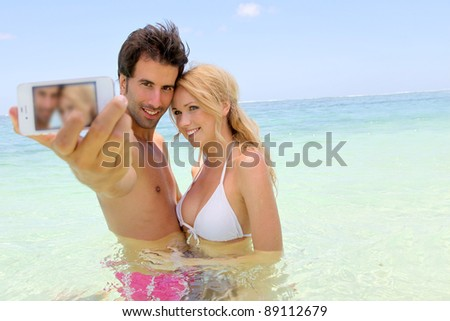 Couple taking picture of themselves in the sea - stock photo