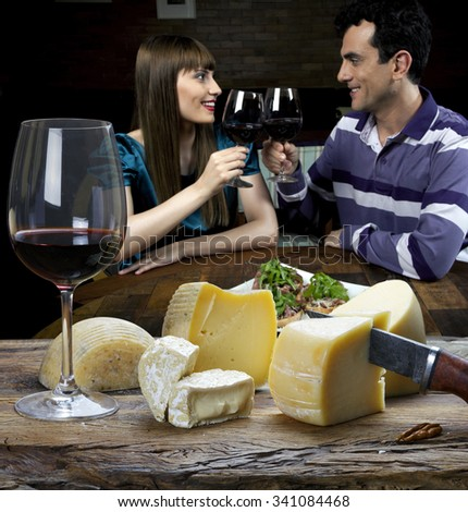 couple taking red wine and eating cheese in the restaurant - stock photo