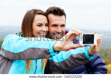 Couple taking self portrait in mountains with smartphone - stock photo