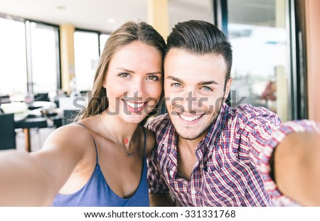 Couple taking self portrait with smart phone. Beautiful young couple selfie - stock photo