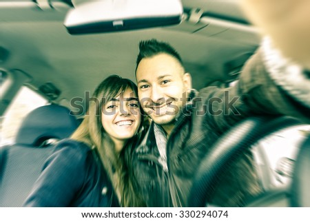 Couple taking selfie inside car - Happy young tourists driving fast and using cell phone - Teenagers students having fun by modern mobile technology - Vintage filtered look with radial zoom defocusing - stock photo