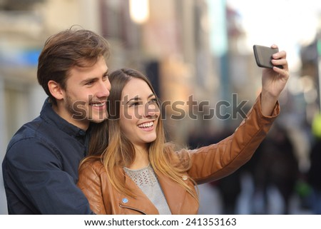 Couple taking selfie photo with a smart phone in the street with an unfocused background