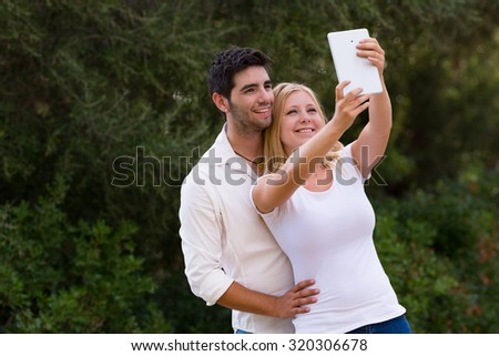 couple taking selfie photo with digital tablet, camera hole moved from the corner to the center  - stock photo
