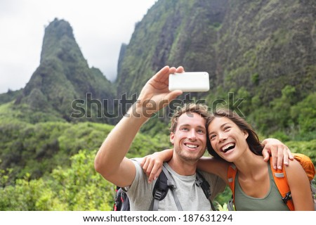 Couple taking selfie photo with smart phone hiking on Hawaii. Woman and man hiker taking photo with smart phone camera. Healthy lifestyle from Iao Valley State Park, Wailuku, Maui, Hawaii, USA. - stock photo