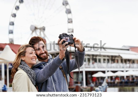 couple taking selfie picture photo at ferris wheel on vacation