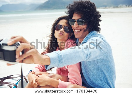 couple taking selfie self portrait at the beach with retro hipster camera - stock photo