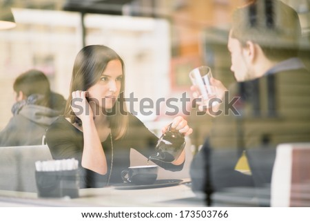 Couple talking and drinking tea in coffee shop