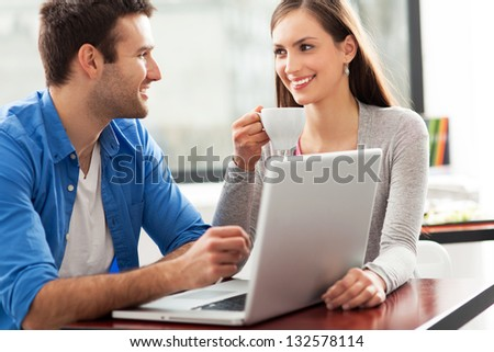 Couple talking and using laptop at cafe - stock photo