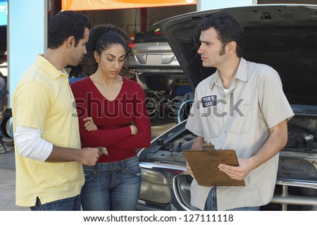 Couple talking to mechanic in front of open car hood
