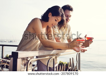 Couple talking while having spritz in a lake view terrace - stock photo