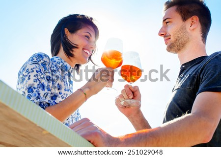Couple talking while having spritz in a seafront - stock photo