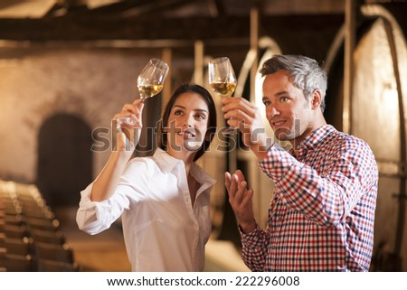 Couple tasting a glass of white wine in a traditional cellar surrounded by wooden barrels. - stock photo