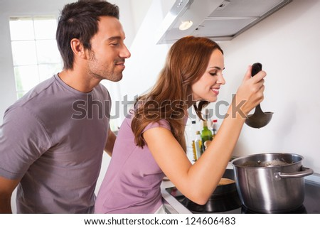 Couple tasting their dinner in kitchen