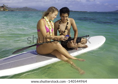 couple texting on a paddle board in the ocean - stock photo