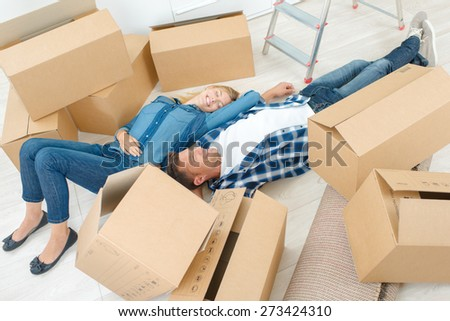 Couple tired from moving house - stock photo