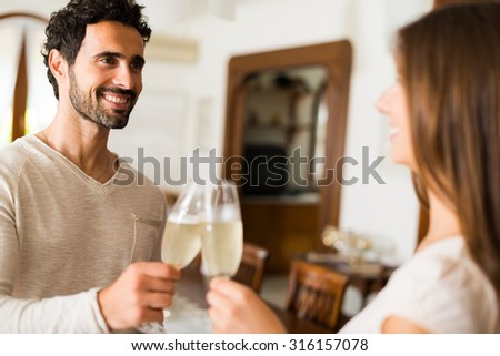 Couple toasting champagne flutes in their apartment. Shallow depth of field, focus on the man