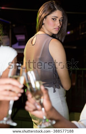 Couple toasting champagne glasses while unhappy looking at them in bar - stock photo