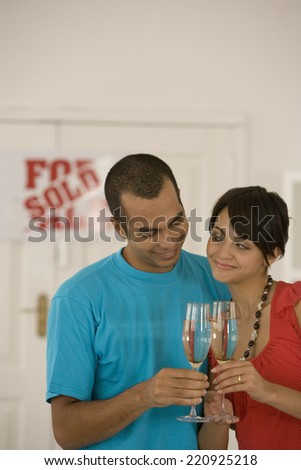 Couple toasting in new house - stock photo