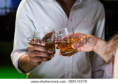 Couple toasting their whisky glasses in bar - stock photo