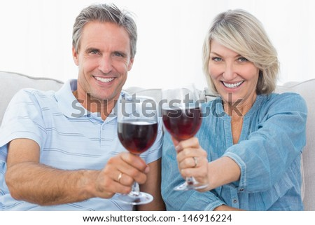 Couple toasting to the camera with red wine on the sofa at home in living room - stock photo