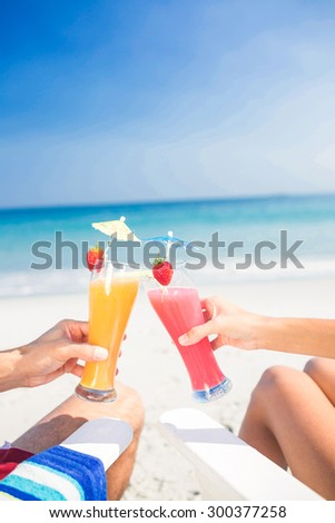 Couple toasting together at the beach on a sunny day