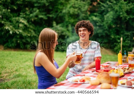 Couple toasting together during the lunch with friends. - stock photo