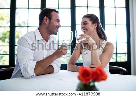 Couple toasting wine glasses at dining table in a restaurant - stock photo