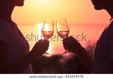 Couple toasting wine glasses in romantic date setting. - stock photo