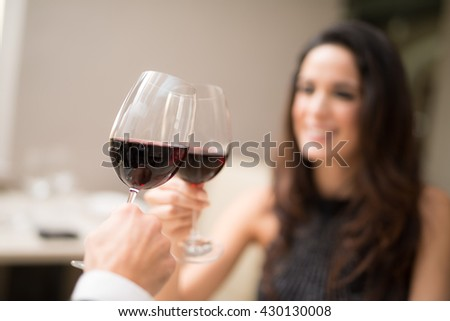 Couple toasting wineglasses in a luxury restaurant. Focus on the wineglass