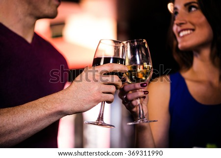 Couple toasting with a glass of wine in a bar