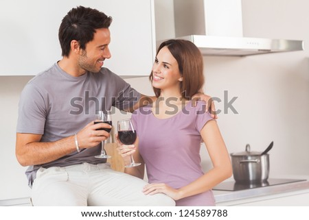 Couple toasting with a glass of wine in kitchen