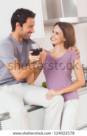 Couple toasting with arms crossed with a glass of wine in kitchen - stock photo