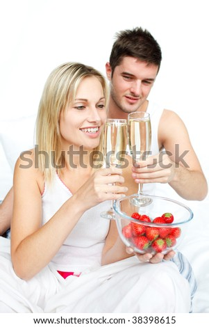 Couple toasting with champagne to an engagement  in bed