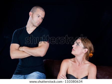 Couple together and angry at each other, he has his arms crossed and they are glaring at each other
