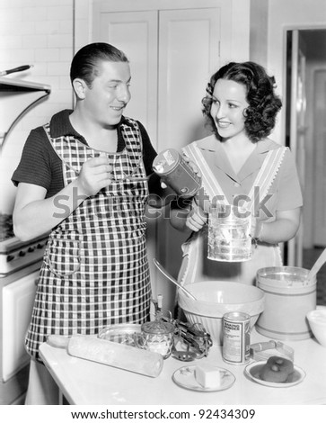 Couple together in the kitchen baking a cake - stock photo
