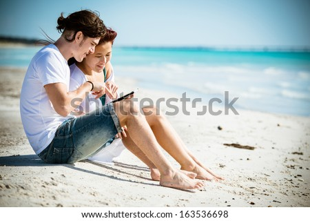 Couple togetherness surfing with tablet on the beach - Stock Image - stock photo
