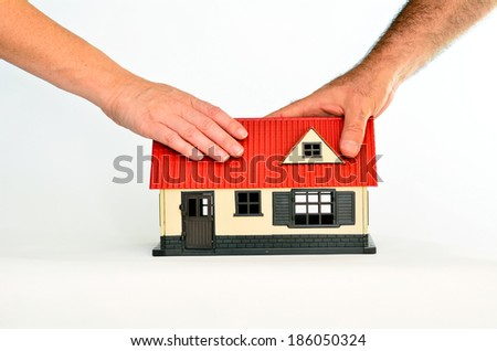 Couple touch a toy house isolated on white background - copy space.Concept photo of real estate business, home  Insurance, house rental,buying, renting, mortgage, finance,service and repair costs - stock photo