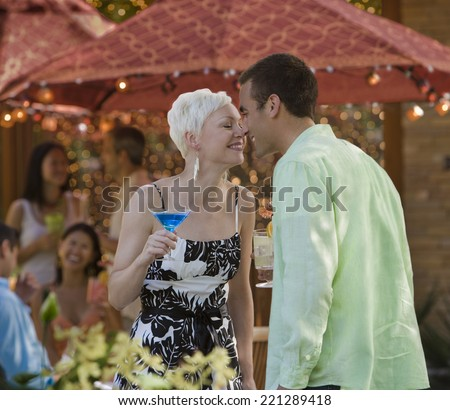 Couple touching noses at party - stock photo