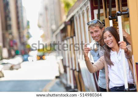 Couple tourists riding the popular touristic attraction cable car system in San Francisco city, California during summer travel holidays. People having fun taking selfie picture and tourist photos.