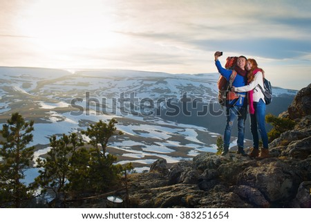 couple tourists woman and man make  selfie in mountains at sunset - stock photo