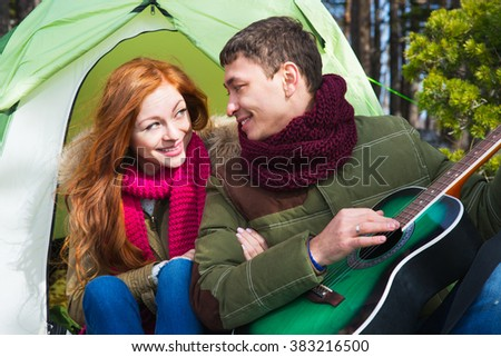couple tourists woman and man sitting at the camp in the forest and mountains