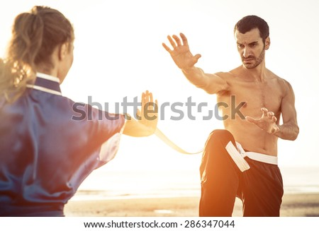 couple training martial arts on the beach. concept about sport and people - stock photo