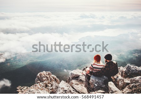 Couple travelers Man and Woman sitting on cliff relaxing mountains and clouds aerial view  Love and Travel happy emotions Lifestyle concept. Young family traveling active adventure vacations